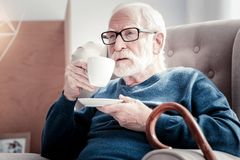 Pleasant elderly man taking a sip. Fragrant tea. Pleasant nice elderly man holding a cup of fragrant tea and taking a sip while enjoying his rest Stock Images
