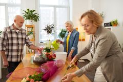 Pleasant elderly people being engaged in floristry. Common interests. Pleasant elderly people standing around flowers while being engaged in floristry stock images