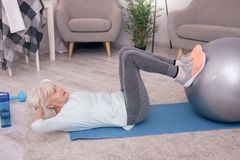 Pleasant elderly woman doing sit-ups. I want six-pack. Beautiful elderly woman doing sit-ups while lying on the yoga mat at home and resting her feet on the Stock Photo