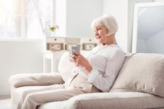 Pleasant elderly woman drinking tea on couch. Cozy morning. Charming elderly women sitting on the comfortable couch, holding a cup of coffee and looking at Royalty Free Stock Image