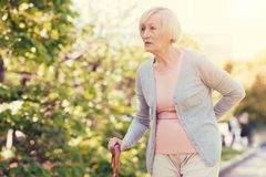 Pleasant elderly woman holding her back Royalty Free Stock Photo
