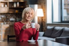 Pleasant elderly woman looking curious while drinking tea Stock Photography