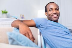 Delighted positive man feeling happy. Pleasant emotions. Delighted joyful positive man smiling and feeling happy while enjoying his time at home Royalty Free Stock Photography