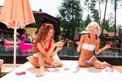 Delighted joyful nice women playing cards together stock images