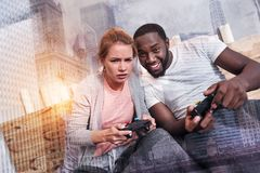Happy nice coupe playing video games. Pleasant entertainment. Happy cheerful nice women sitting together and playing video games while resting at home Stock Images