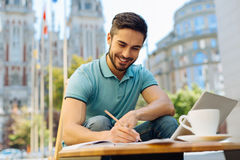 Pleasant excited man working on something interesting. Creating something extraordinary. Dedicated motivated bright guy feeling inspired and making some notes Royalty Free Stock Photo