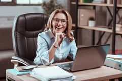Pleasant experienced lawyer feeling excited before work. Excited before work. Pleasant experienced lawyer sitting at the table feeling excited before work stock photos