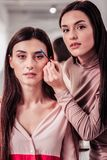 Pleasant experienced makeup artist giving professional advice. Beautiful eyebrows. Pleasant experienced makeup artist standing near her client while giving her stock photos