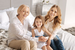 Pleasant extended family bonding on the bed. Sense of togetherness. Charming young women and her sophisticated mother holding hands around the pretty little girl stock images