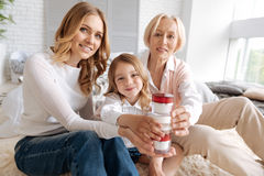 Pleasant extended family creating a tower with cream jars royalty free stock images