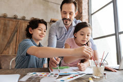 Pleasant family being immersed into painting process Royalty Free Stock Photos