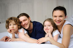 Pleasant family morning. Mother, father and two children lie in an embrace on a bed. Love and tenderness Stock Photo