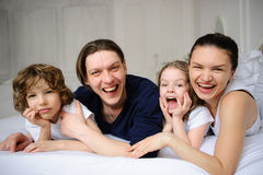 Pleasant family morning. Mother, father and two children lie in an embrace on a bed. Love and tenderness Stock Images