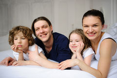 Pleasant family morning. Mother, father and two children lie in an embrace on a bed. Love and tenderness Royalty Free Stock Photo