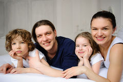 Pleasant family morning. Mother, father and two children lie in an embrace on a bed. Love and tenderness Stock Image