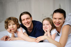 Pleasant family morning. Mother, father and two children lie in an embrace on a bed. Love and tenderness Royalty Free Stock Photography