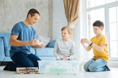 Pleasant family preparing plastic bottles for recycling. Care about nature. Cheerful pre-teen boys and their young father sitting on the floor, crushing the Stock Photo