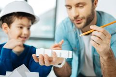 Pleasant father and son scrutinizing 3D house layout. Examining thoroughly. The focus being on the 3D house layout in the hand of a charming young father Royalty Free Stock Photography