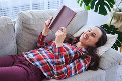 Pleasant female having rest while reading book Stock Photo