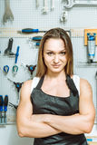Pleasant female mechanic demonstrating her sporty body in the workshop Stock Image