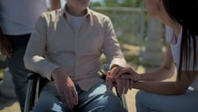Pleasant female volunteer holding hand of a retired wheelchaired man stock footage