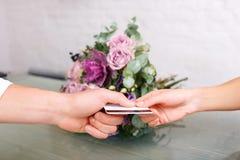 Pleasant florist serving client Royalty Free Stock Images