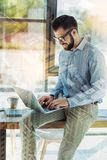 Pleasant friendly man sitting on the table and using laptop. New program. Pleasant friendly bearded man sitting in the room on the table working with the laptop Stock Photos