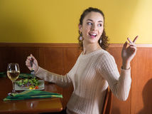 Pleasant girl calls up the waiter in a restaurant Royalty Free Stock Photos