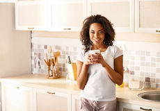 Pleasant girl drinking tea in the kitchen Royalty Free Stock Photos
