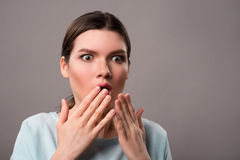 Pleasant girl expressing surprise on grey background Stock Image