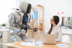 Pleasant girl getting package from the robot Stock Photography