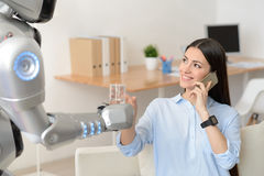 Pleasant girl getting water from the robot Royalty Free Stock Images