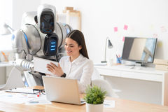Pleasant girl and robot using tablet Stock Photos