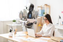 Pleasant girl and robot working in the office Stock Photo