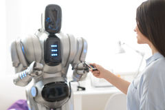 Pleasant girl standing with robot. Switch it on. Smiling delighted beautiful girl holding remote control and expressing gladness while robot standing in the royalty free stock photos
