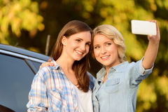 Pleasant girls standing near car Royalty Free Stock Photography