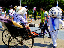 Pleasant Goat Cartoon characters cosplay. Pleasant Goat Cartoon characters pushing a cart with tourist sitting on it in May Fourth Square in Shandong province royalty free stock photos