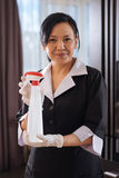 Pleasant good looking hotel maid using the cleansing agent Stock Photography