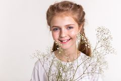 Pleasant good-looking kid looking happy while carrying field flower. Appealing young lady. Pleasant good-looking kid looking happy while carrying field flower stock photo