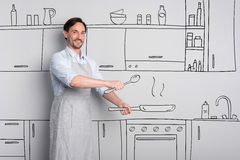 Pleasant good looking man holding a frying pan stock photo