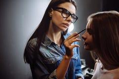 Pleasant good looking visagiste applying eyebrow makeup Royalty Free Stock Image