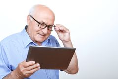 Pleasant grandfather surfing through the Internet royalty free stock images