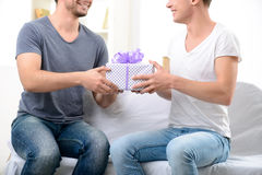 Pleasant guy giving present to his male partner Stock Photos
