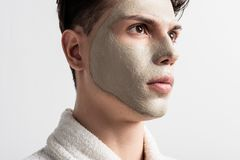 Pleasant guy is having facial therapy. Anti-aging treatment. Side view of young serious man is standing in bathrobe with facial clay mask. He is looking aside royalty free stock image