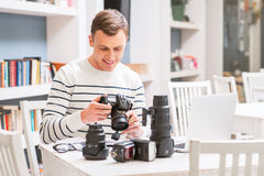 Pleasant guy holding photo camera Stock Photography
