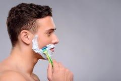 Pleasant guy shaving Stock Images
