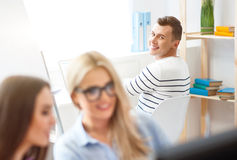 Pleasant guy working in the office. Have a nice day. Cheerful overjoyed smiling guy sitting at the table in the office and expressing gladness while working with Stock Photography