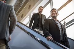 Pleasant guys are descending on escalator royalty free stock image