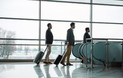 Pleasant guys are walking with luggage to escalator stock photos