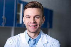 Pleasant handsome scientist standing and smiling. Satisfied scientis. Young handsome unshaken scientist in a labcoat standing in the room smiling and looking Royalty Free Stock Photo